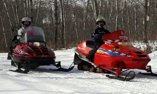 Two children ride snowmobiles in the woods