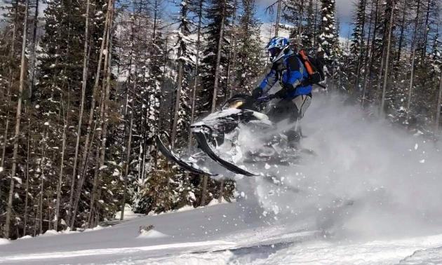 A snowmobile gets big air, leaving a powder trail in its wake.