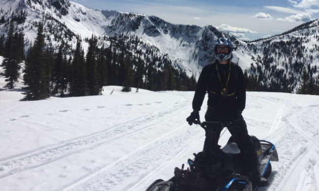 A snowmobiler stands on his ride on a snowmobile trail with mountains in the background.