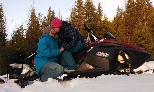 Drew and Liane Leger kiss each other while sitting on a snowmobile.