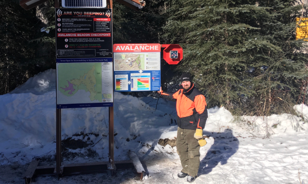 Les L'Heureux stands next to a solar-powered transceiver checker, complete with parks signage and avalanche awareness.