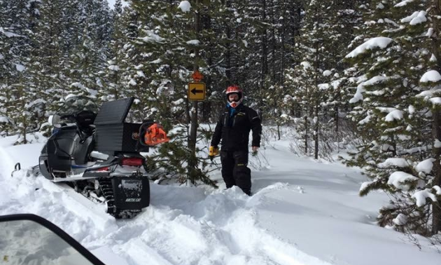 A man stands next to a sign and his parked snowmobile on a snowmobile trail.