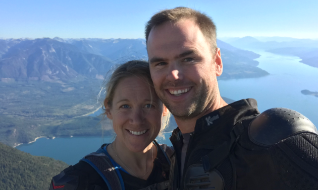 Matt Elliott and Sarah Blancher smile from a high vantage overlooking a lake and mountains.