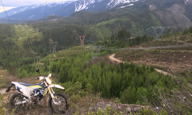 A dirt bike is parked on top of a big mountain.