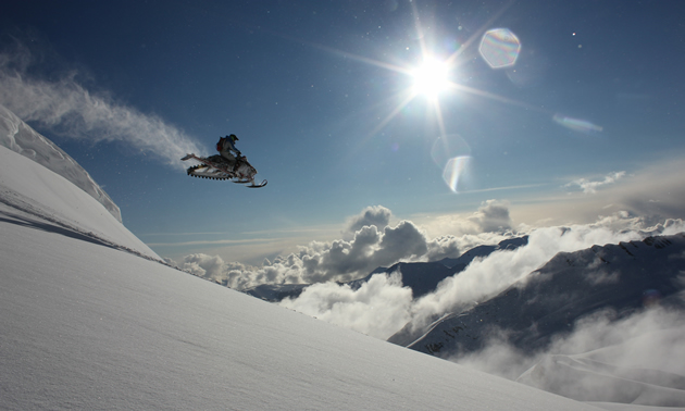 A snowmobiler gets massive air off a mountain as the sun shines overhead.