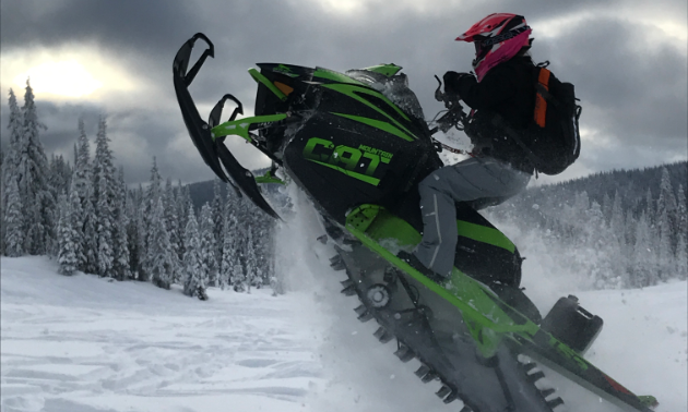 "Meghan Bosecker pulls a wheelie on her green and black 2018 Arctic Cat M8000 Mountain Cat 153""."