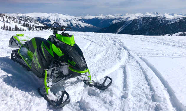 "A green and black 2018 Arctic Cat M8000 Mountain Cat 153"" is parked in the snow on top of a mountain."