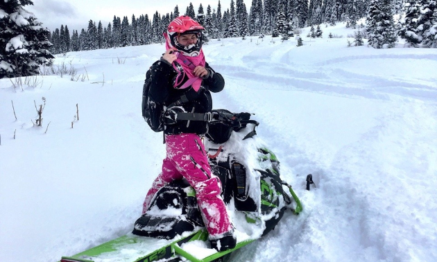 Meghan Bosecker wears pink and black riding gear while standing on her snowmobile on a trail.