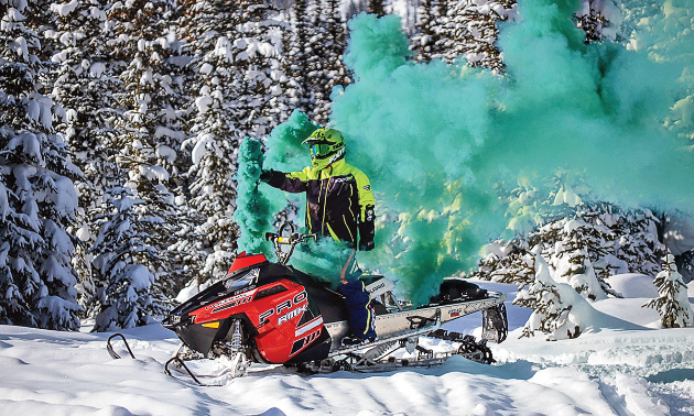 A woman stands on a snowmobile with a blue plume of smoke trailing behind her.