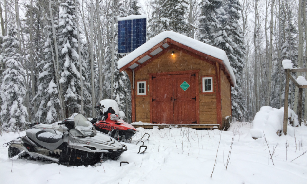 A wooden shelter with two snowmobiles parked up front.