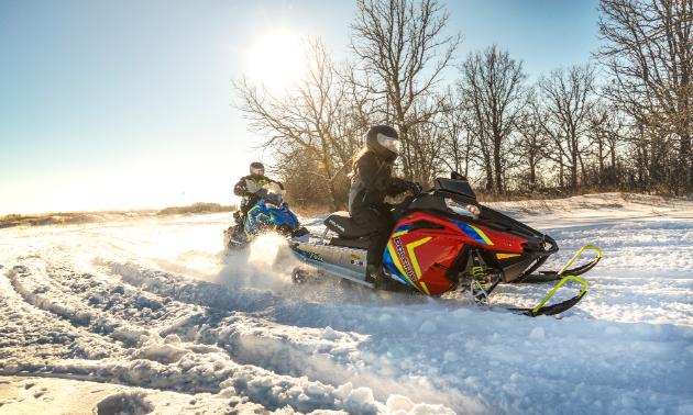 Polaris Indy Evos ride through the snow.