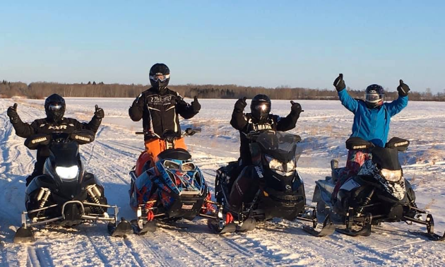 Four snowmobilers throw up their hands in a happy pose.