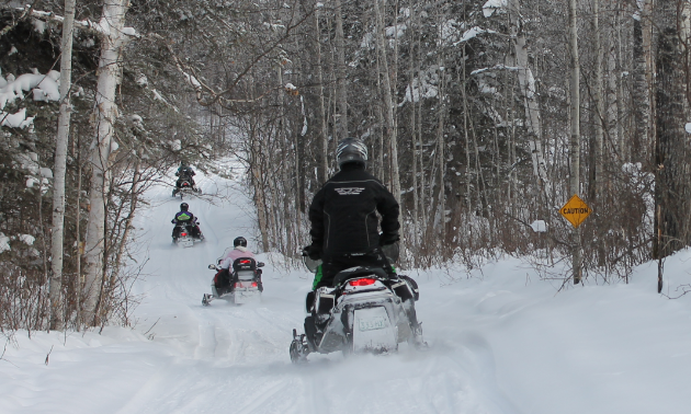 Snowmobilers ride along a trail.