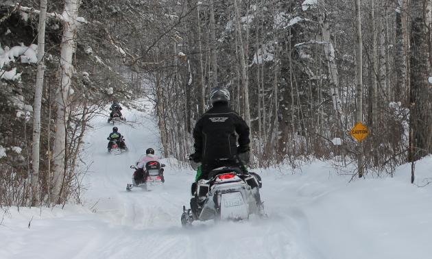 Snowmobilers ride along a trail.