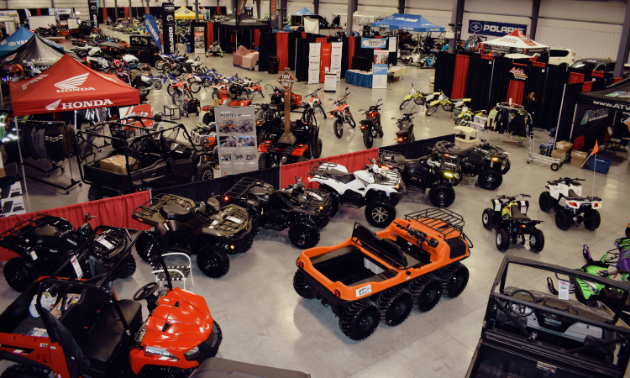ATVs and motorcycles are lined up on a showroom floor