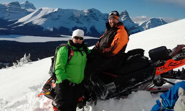 Les and Amanda L'Heureux smile on their snowmobiles with mountains in the background.