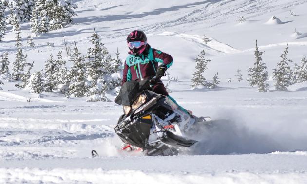 A woman rides a snowmobile through the woods.
