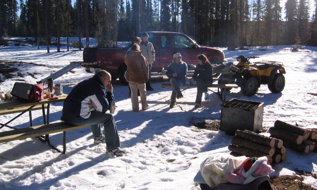 A family takes a break at picnic tables in the snow. A truck and ATV are parked nearby.