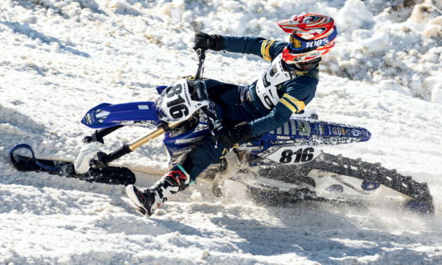 A blue and white snow bike leans into a tight turn.
