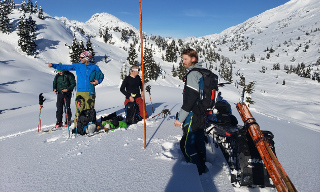 Ryan Thorley and others stand near an orange bamboo pole on a snow-covered mountain.