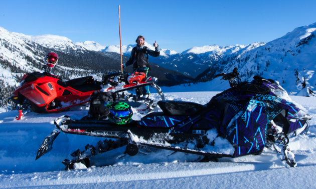 Ryan Thorley stands next to an orange bamboo pole with two snowmobiles in the foreground and snow-capped mountains in the background.