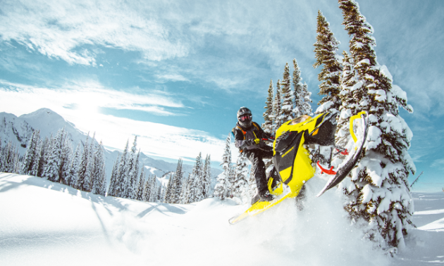 A snowmobiler gets air on a yellow Ski-Doo Summit 850 E-TEC.
