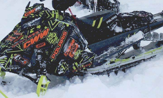 A black snowmobile with neon green and orange writing on the sides.