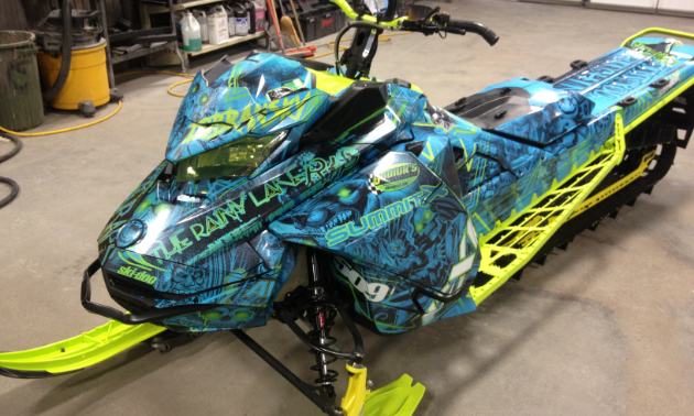 A beautiful blue sled wrap lined with neon green on a snowmobile.