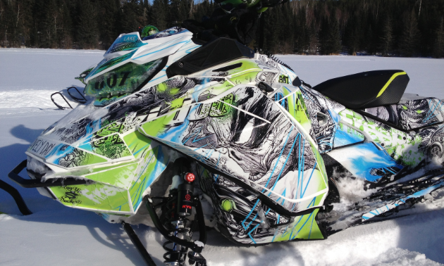 A white, green and blue sled wrap on a snowmobile.