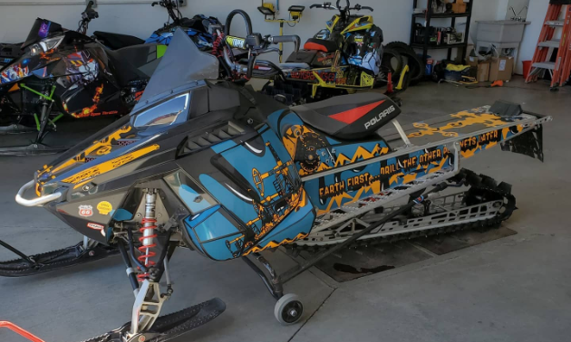 A black, blue and orange sled wrap on a snowmobile.