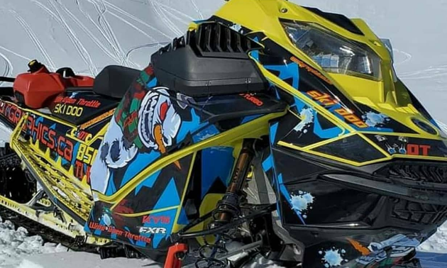 A neon green snowmobile with an angry snowmobile sticker on the side.