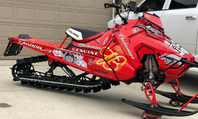 A red snowmobile with Budweiser ads on the side of the machine.