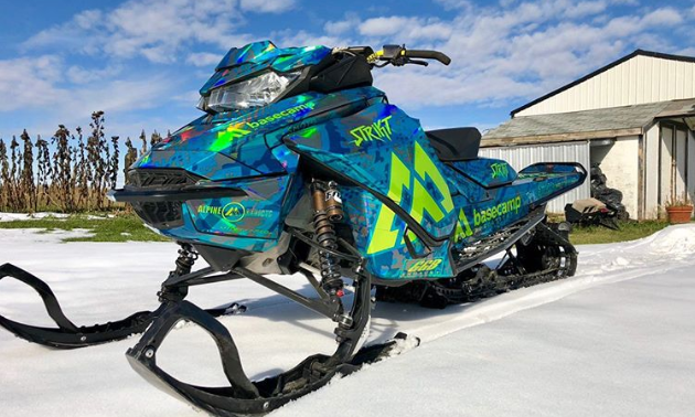 A bluish-green sled wrap on a snowmobile on a beautiful bluebird day.