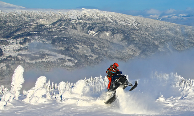 A snowmobiler ascends a mountain to climb out of a bowl of snow.