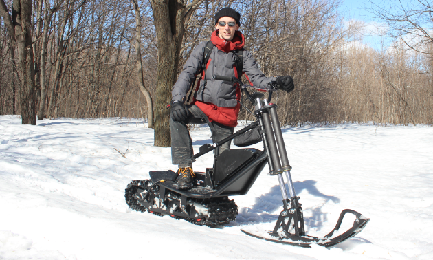 A man poses on an electric snow scooter.