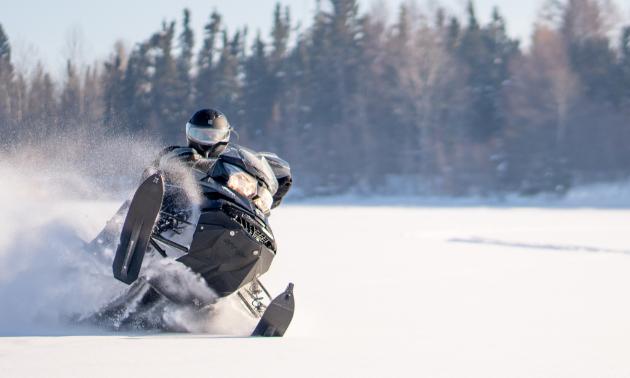 A snowmobiler gets air in a field.