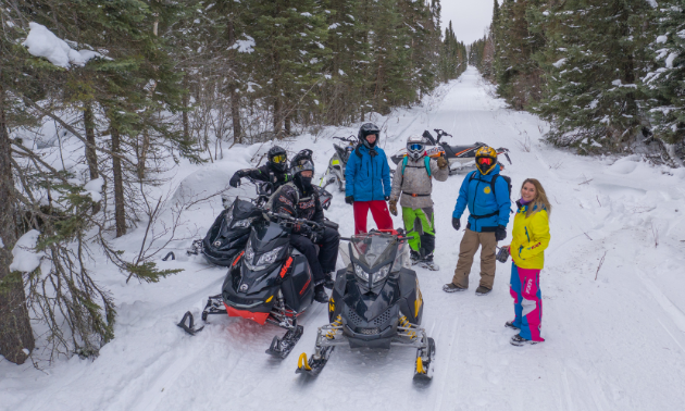 A group of snowmobilers take a break on a trail.