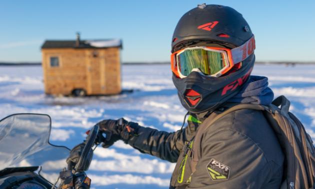 A snowmobiler stops near a warm-up shelter.