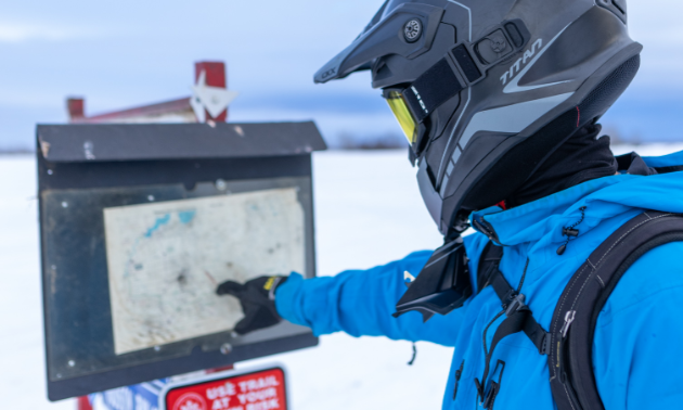 A snowmobiler points to a trail map.