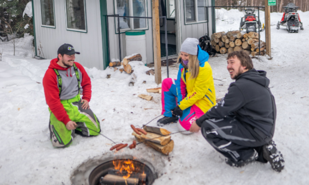 Ashlyn George and her friends enjoy a hot dog roast by a fire next to a warm-up shelter.