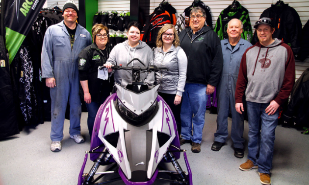 A group of workers pose behind a snowmobile inside Universe Satellite Sales.