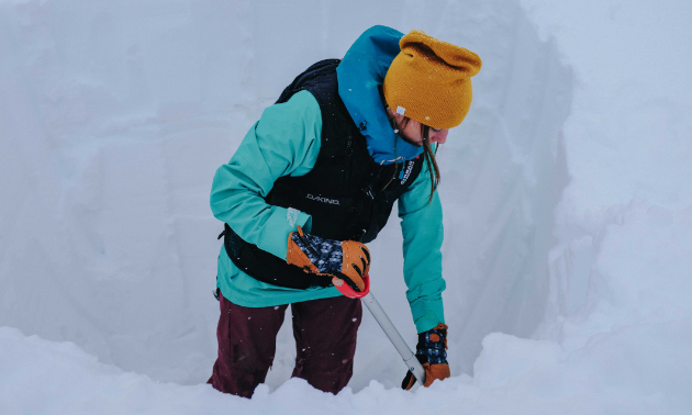 Brittney Dickson demonstrates how to evaluate snowpack safety by digging a snow pit.