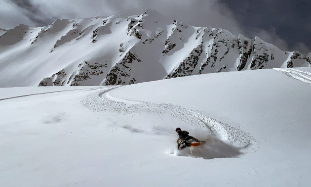 A snowmobiler shreds through fresh snow.
