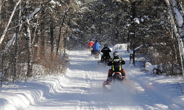 Snowmobilers in Manitoba enjoy a sunny afternoon ride.
