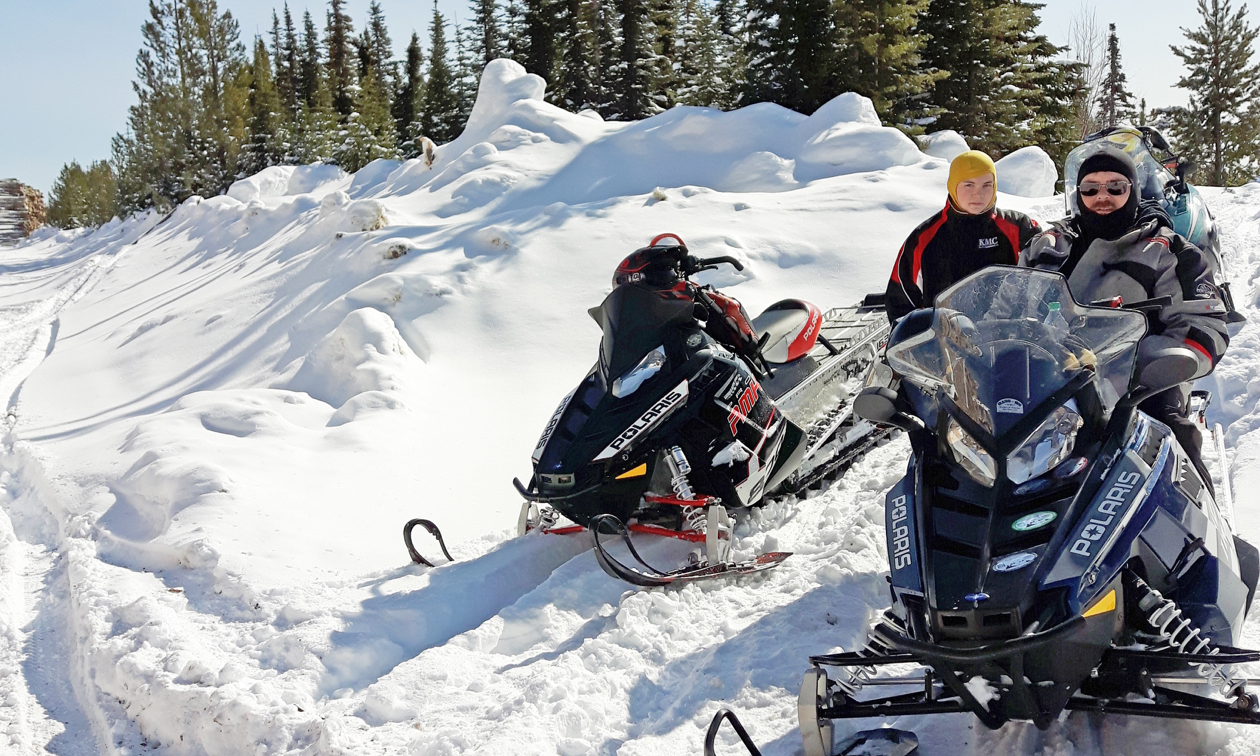 A couple of riders take a break on their snowmobiles.