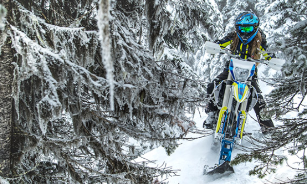 A blue and yellow snow bike makes its way through snow-covered trees.