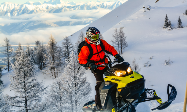 A snowmobiler ascends a mountain on his sled.