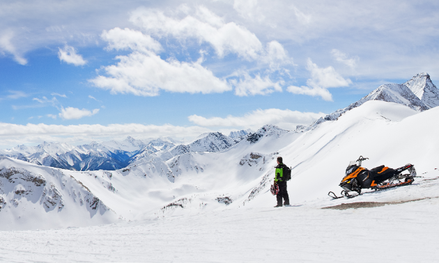 A snowmobiler gets off his sled to take in a view of the mountains.