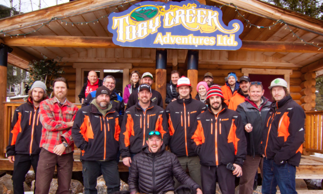The staff of Toby Creek Adventures pose in front of a cabin with the name of the business on it.