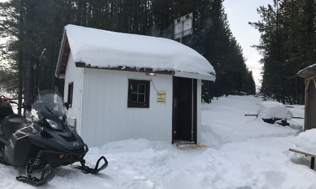 A black snowmobile is parked next to a small white warm-up shelter.
